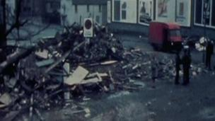 Rubble and a red van on the street after the blast