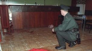 An officer sits and looks at the bloodied floor of the bar