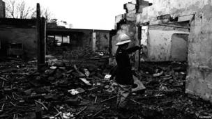 A fireman stands in the ruins of the La Mon Hotel