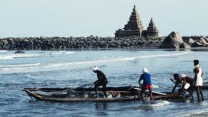 Fishermen in front of the temple on the coast of the Mamallapuram complex in India by Adam Woolfitt