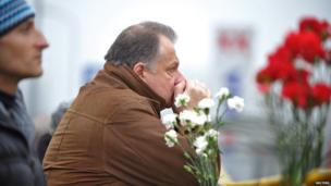 A man waits for news at the scene where the Maxima supermarket roof collapsed in Riga on November 22, 2013