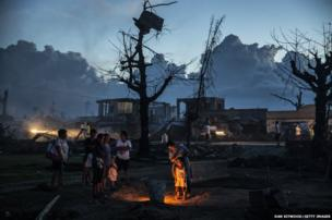 A family gather around a grave of a relative whowas killed when Typhoon Haiyan struck their home in Leyte, Philippines