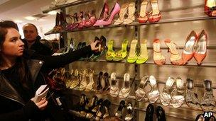 A woman reaches for a pair of shoes in a charity shop