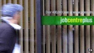 A person - out of focus - walks past a job centre