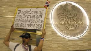 An anti-government protester blows a whistle and holds a placard during a rally at Thailand's Finance Ministry in central Bangkok, 25 November 2013
