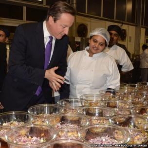 British Prime Minister David Cameron inspects the kitchen and meets the chefs at the British curry awards at Battersea Evolution in London