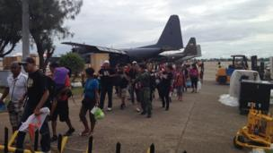 People walking off military planes