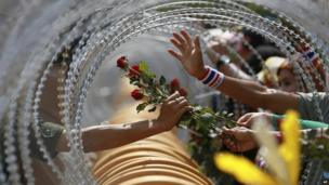 An anti-government protester gives a rose to a Thai soldier at the defence ministry during a rally in Bangkok