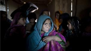 An Afghan refugee girl attends with other children her class at a makeshift school set up in a mosque on the outskirts of Islamabad, Pakistan, Thursday, Nov. 28, 2013.