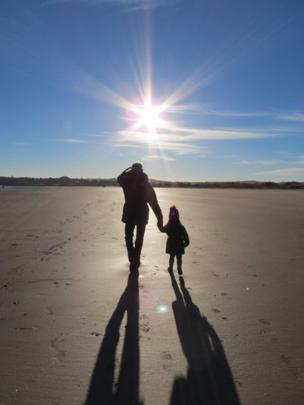 Girl and her dad on the beach