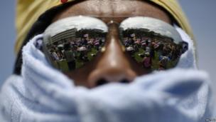 Anti-government protesters are reflected in the lens of a demonstrator's sunglasses after breaking into the compound of the Royal Thai Army headquarters, 29 November 2013.