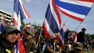 Anti-government protesters hold national flags after breaking into the compound of the Royal Thai Army headquarters in Bangkok, 29 November 2013