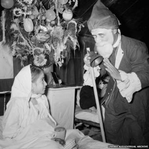 Man dressed as Father Christmas visiting a young girl in Jordan's Amman New Camp (1971)