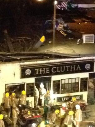 Wreckage of helicopter visible on pub roof