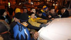 Protesters block a police car holding detained people