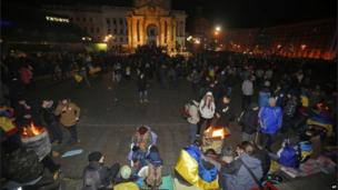 Ukrainian protesters gather over barrels with bonfires to warm themselves before police arrived.
