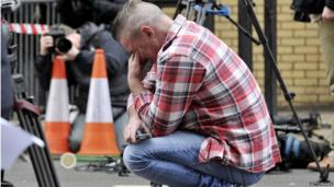 Paul Watt, a regular at the Clutha pub, reacts at the police cordon set up around the site of a helicopter crash on the Clutha in the centre of Glasgow
