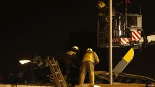 Two firemen working on the roof of a pub where a helicopter crashed. Another fireman is on a platform above them