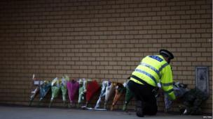 A police officer lays a bunch of flowers against a wall where more bunches of flowers have already been placed