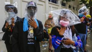 Anti-government protesters use plastic bags to cover their heads during a clashes with the police at the metropolitan police headquarters in Bangkok, 2 December 2013