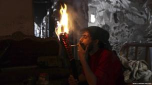 A Free Syrian Army fighter lights a cigarette