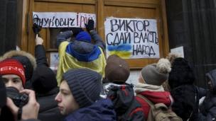 Protesters put posters vilifying President Yanukovych and urging him to give up power at government headquarters in Kiev 02/12/2013