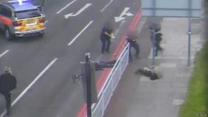 Michael Adebowale raising his gun, while on the ground
