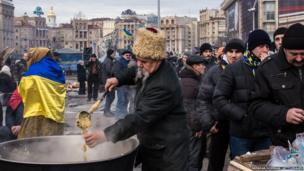 A man serves food to anti-government protesters in Independence Square on December 4, 2013 in Kiev, Ukraine