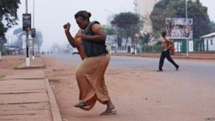 A woman runs from gunfire in Bangui December 5, 2013