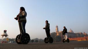 Women ride two-wheeled self-balancing scooters past the Indian Defence Ministry, in New Delhi