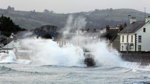 Waves hit a sea wall, sending spray high into the air