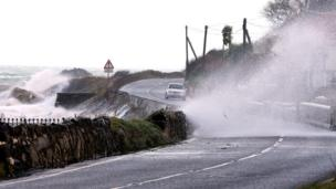 High winds and the sea batter the Antrim coast road, in County Antrim, Northern Ireland