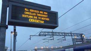 Train station sign reading 'all services now cancelled'.