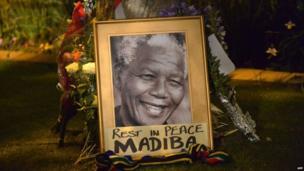 Flowers near a framed image of Nelson Mandela in Johannesburg. Photo: 6 December 2013