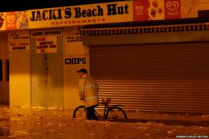 A man pushes his bicycle through flood water during a storm surge in Great Yarmouth