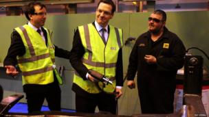 Britain's Chancellor of the Exchequer George Osborne uses a stud gun during a visit to JCB's backhoe loader factory in Rocester, Staffordshire