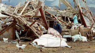 Survivors search for belongings in the rubble of their house, near the bodies of victims, after an earthquake hit the Armenian town of Spitak, on December 11, 1988.