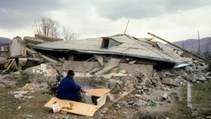 A Survivor sits near his house in the devastated town of Spitak, on December 11, 1988, after an earthquake hit Armenia, on December 7, 1988.
