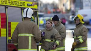 Fire services personnel stop for a cup of tea after a night working in flooded streets in Lowestoft, Suffolk