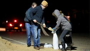 Local residents fill sandbags through the night as high tide approaches in Great Yarmouth