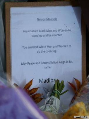 Tributes are placed at the foot of a statue to Nelson Mandela in Parliament Square, London