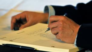David Cameron signs the book of condolence at the South African Embassy in central London