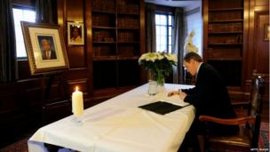 David Cameron signs a book of condolence at South Africa House