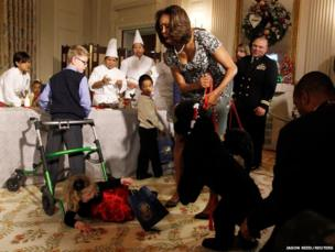 In the White House first lady Michelle Obama reacts as Ashtyn Gardner, 2, loses her balance