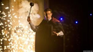 Matt Smith wields a Dalek's eye stalk as an explosion goes off behind him.