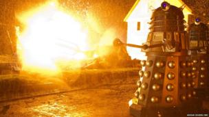 Two Daleks approach as flames erupt behind them.