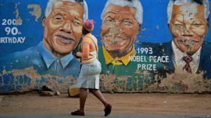 Woman walks past murals of Nelson Mandela in Soweto (7 Dec)