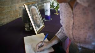Mourner signs book of condolence at Regina Mundi church in Soweto (7 Dec)