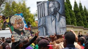 Portraits of Nelson Mandela held up in Houghton