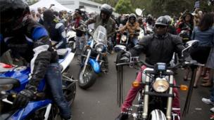 Motorcyclists outside the former home of Nelson Mandela in Johannesburg (8 Dec 2013)